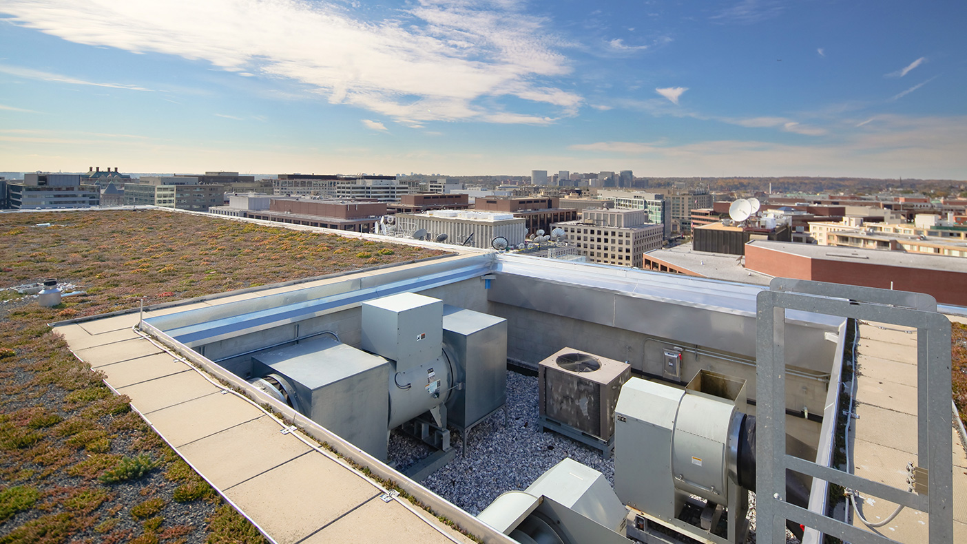 Replacement cooling towers are situated below the elevation of the building's green roof so as to limit their visibility from the street, adjacent buildings, and roof-level terrace.