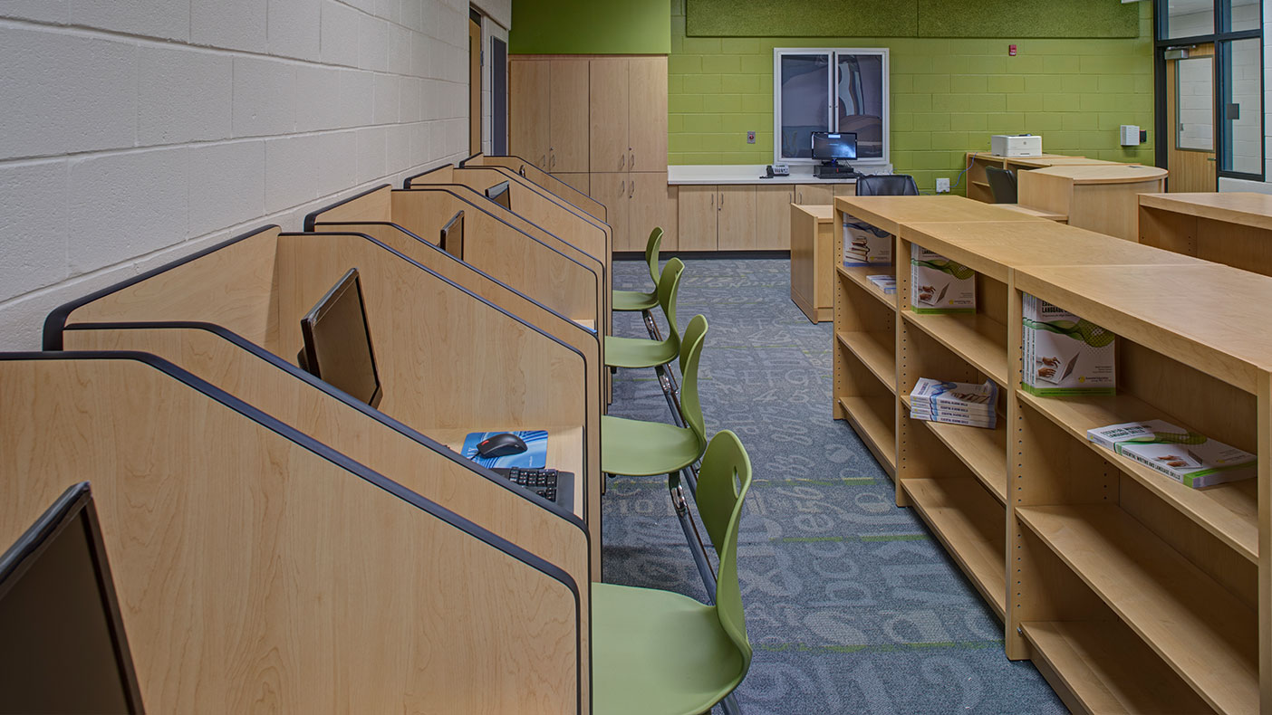 The new library in the center includes individual work stations, each equipped with a computer and multiple bookcases.
