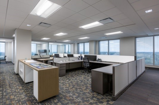 Low-partitioned cubicles are surrounded by glass-enclosed offices to facilitate daylighting.