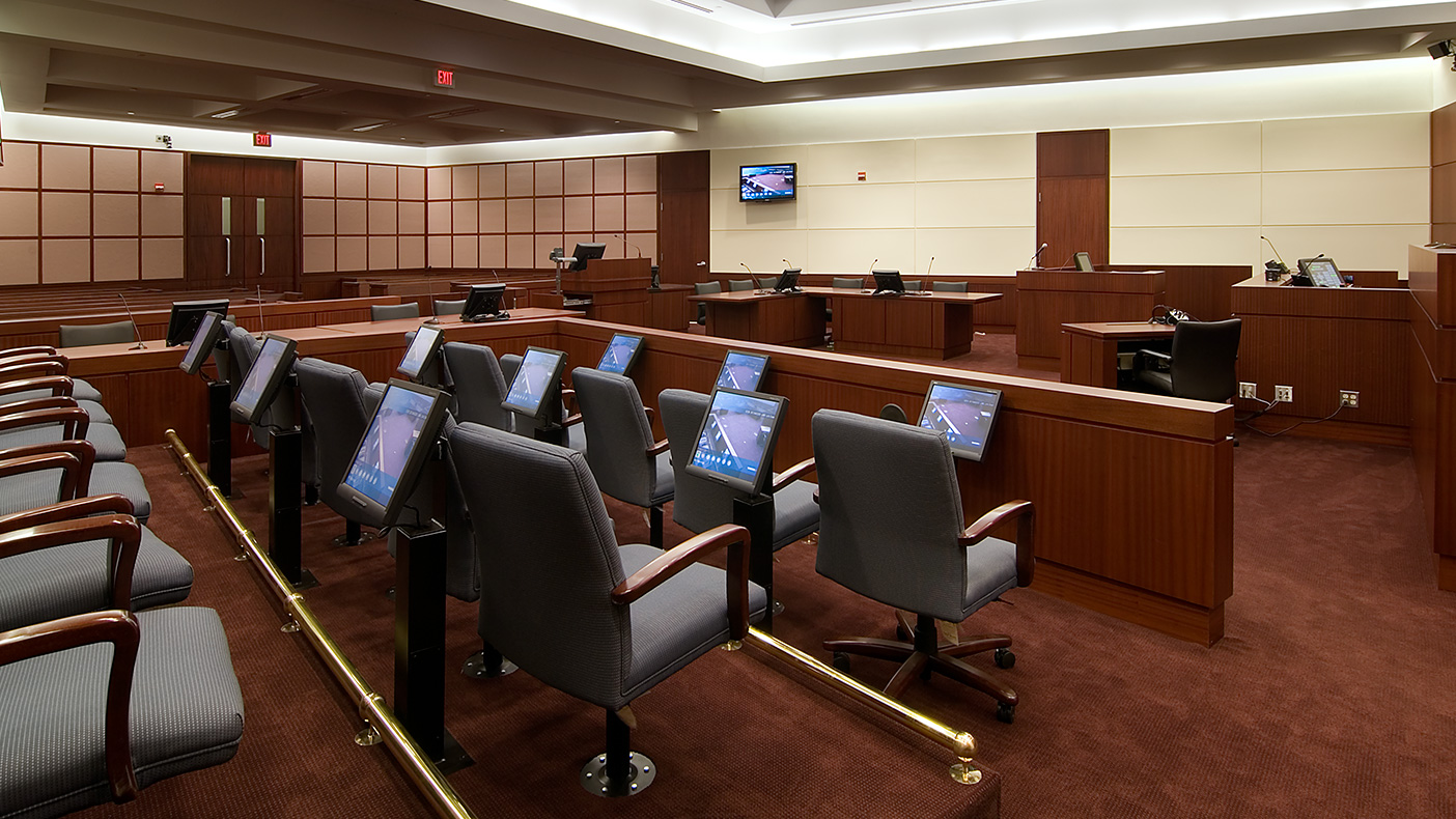 U.S. District Courtroom 2B includes fixed evidence presentation systems for each jury member and large screens for spectators. Systems are fully integrated into the casework for the attorney tables, lectern, and judge's bench.
