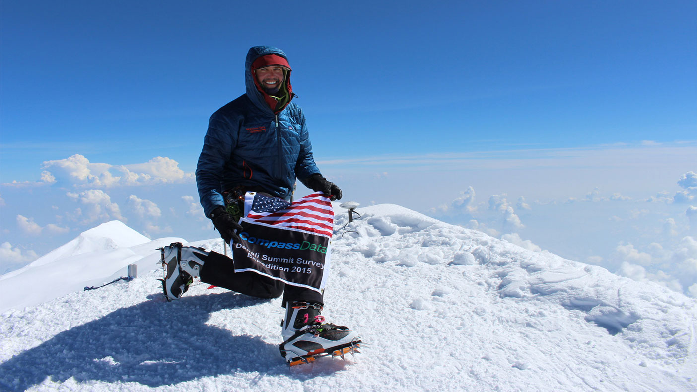 Blaine Horner, survey party chief with CompassData at the summit on June 24, 2015, places a GPS antennae at the summit of Denali for future data collection.
