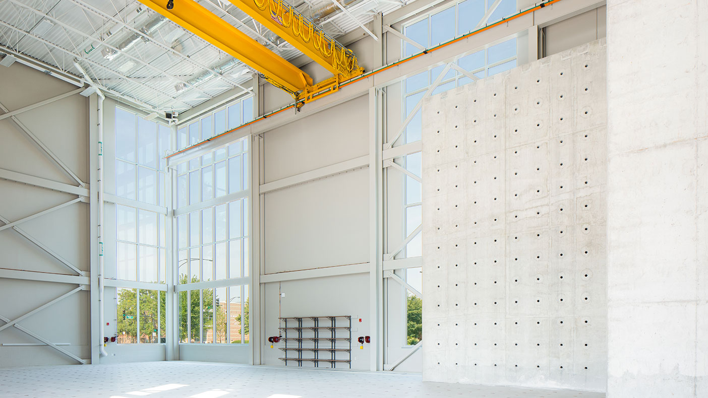 The building features a high-bay structural testing laboratory with a 30-foot high concrete reactive wall and a six-foot-thick concrete strong floor.